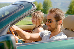 A young couple in a convertible car Stock Images