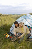 Young couple cooking at campsite Royalty Free Stock Image