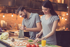 Young couple cooking in kitchen royalty free stock photos