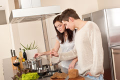Young couple cooking in kitchen together Stock Photos