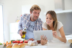 Young couple cooking in the kitchen using tablet Royalty Free Stock Photos