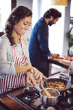 Young couple cooking. Man and woman in their kitchen Royalty Free Stock Photos
