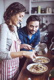 Young couple cooking. Man and woman in their kitchen Stock Image