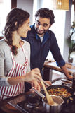 Young couple cooking. Man and woman in their kitchen Stock Images