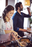 Young couple cooking. Man and woman in their kitchen Royalty Free Stock Images