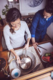 Young couple cooking. Man and woman in their kitchen Royalty Free Stock Image