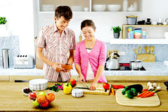 Young couple cooking - Men and women in the kitchen preparing food Royalty Free Stock Image