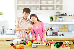 Young couple cooking - Men and women in the kitchen preparing food Stock Image