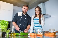 A young couple is cooking in their kitchen, looking at the camera. stock photos