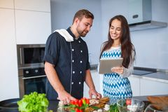 A young couple is cooking in their kitchen, with a tablet. stock photos