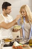 Young couple cooking together in kitchen Stock Photos