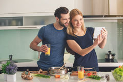 Young couple cooking together meal preparation indoor Stock Images