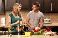 Young couple cooks in kitchen Stock Photography