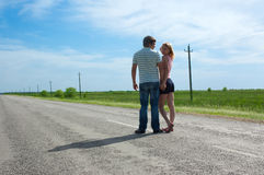 The young couple costs on the road Royalty Free Stock Images