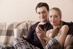 Young couple on a couch Stock Photos