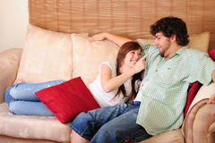 Young couple on couch. Young couple relaxing on a couch and having fun. Girl pointing towards the boy playfully stock photos