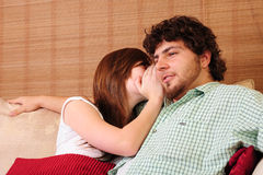 Young couple on couch. Young couple relaxing on a couch. Girl whispering into the boy's ear royalty free stock images