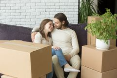 Young couple on couch moved in new home with boxes. Young happy couple sitting on couch in living room embracing just moved into new home, smiling men and women Royalty Free Stock Photo