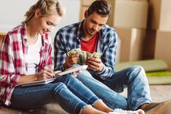 Young couple counting money. While sitting on floor in new apartment Royalty Free Stock Image