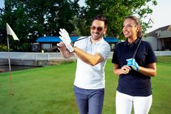 Couple at the course playing golf and looking happy. Young Couple at the course playing golf and looking happy royalty free stock photography
