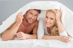 Young couple covering themselves in the duvet Royalty Free Stock Images