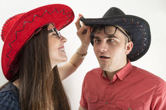 Young couple with cowboy hats and glasses making silly faces on white Royalty Free Stock Image