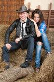 Young couple cowboys on the hay. A young cowboy with sexual girl sitting on the hay royalty free stock photos