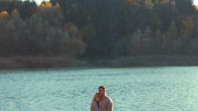 Young couple in cozy elegant sweaters standing on the river bank hugging with love each other. Love story, forever stock video