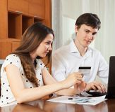 Young couple with credit card at home. Young couple buying something online at home stock photo