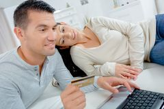 Young couple with credit card and laptop. Young royalty free stock images