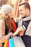 Young couple with credit card shopping in the city. A picture of a beautiful couple shopping with a credit card in the city stock images