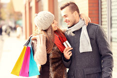 Young couple with credit card shopping in the city. A picture of a beautiful couple shopping with a credit card in the city stock photos