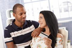 Young couple with credit card smiling. Young mixed couple at home, women holding credit card, looking at each other, smiling royalty free stock photo