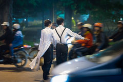 Young couple crossing busy street. Vietnam. Royalty Free Stock Photography