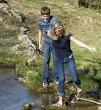 Young couple crossing a creek. Young teen couple attempting to cross a creek without falling in stock photos