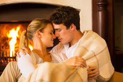 Young couple cuddling. Affectionate young couple in love cuddling near fireplace royalty free stock images