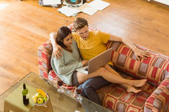Young couple cuddling on the couch with laptop. At home in the living room royalty free stock photo