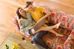 Young couple cuddling on the couch with laptop Stock Photos