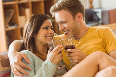 Young couple cuddling on the couch with red wine Royalty Free Stock Photography