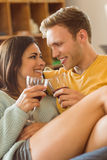 Young couple cuddling on the couch with red wine Royalty Free Stock Images