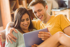 Young couple cuddling on the couch with tablet pc. At home in the living room stock photography
