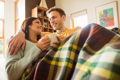 Young couple cuddling on the couch under blanket. At home in the living room Stock Photo