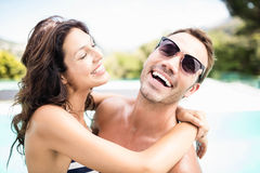 Young couple cuddling each other near pool. At sunny day Stock Photos