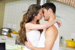 Young couple cuddling in kitchen Stock Image