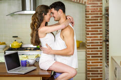 Young couple cuddling on kitchen worktop Royalty Free Stock Photos