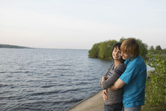 Young Couple Cuddling On Lakeshore Stock Photography