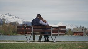 Young couple cuddling on lakeside wooden bench with beautiful mountain view. Rear view. 4k stock footage