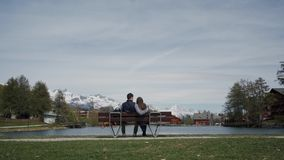 Young couple cuddling on lakeside wooden bench with beautiful mountain view. Rear view. General plan. 4k stock video