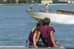 Young couple cuddling while sitting on the pier, Venice, Italy. Europe stock photos