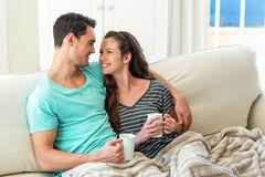Young couple cuddling on sofa while having coffee Stock Images